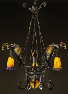"black and gold painted wrought iron centre light with three birds holding floriform glass shades. Signed ""Muller freres Luneville"" and ""Chapelle"". Circa 1925. H : 42 ½ in Diam : 27 ½ in  