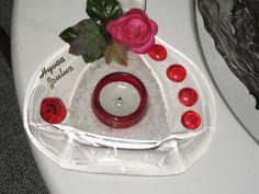 Tuikkualusta tehty lasipullo sulattamalla ja koristelemalla keinokukkasin.