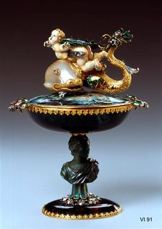 Zierschale with Cupid and Dolphin probably Dresden and Frankfurt, early 18th century.  The small green jasper with two handles is set in gold and studded with rubies, emeralds and diamonds. On the cover, which is enameled inside and outside, there is a dolphin from a baroque pearl and gold enamelled with a flying enameled Cupido about it. The shell rests on a cut of jasper and decorated with diamonds bust.