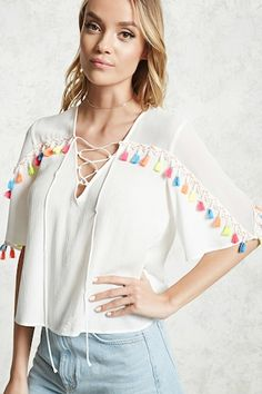 A woven top featuring a front multicolor tassel trim, a sheer chiffon yoke, lace-up V-neck, short sleeves, and a relaxed fit.