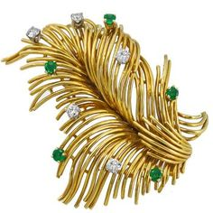 This is a wonderful 18k yellow gold Tiffany & Co pin from the 1960s. The pin features a feather motif with sparkling round cut diamonds and emeralds that weigh approximately 0.50ct and 0.40ct respectively. The color of the diamonds is F with VS clarity. The pin is signed Tiffany 18K. It measures 47mm by 37mm and 19.1 grams.