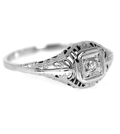 This sweet ring from the 30's features a 0.05 carat Old European cut diamond surrounded by hand engraving and intricate filigree design.