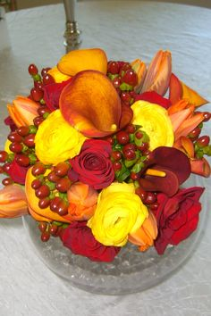 Bridal bouquet with red roses, yellow ranunculas, mango callas, orange tulips & brown hypericum berries