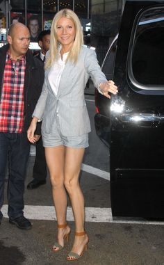 Gwyneth Paltrow showcases her long legs in a flattering gray shorts suit and a pair of color-block ankle strap sandals.