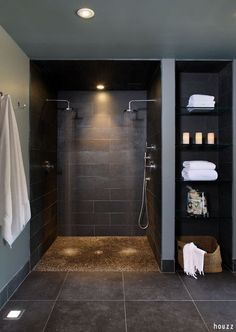 Relaxing walk in shower with pebble flooring and two rain shower heads for extra comfort! Try our cost estimator and see how much a shower remodel in your area costs!