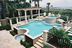 Classic geometric pool with elevated spa, stone decking, waterfall, planters, and pergola | Year Round Pools Company, Inc., Bluffton, SC  http://www.luxurypools.com/swimmingpoolbuilder/Year-Round-Pool-Company-Inc?fid=433