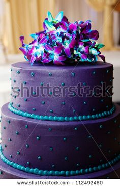 stock photo : Three tier purple wedding cake with blue trim and flowers: Might want white with blue and purple trim to keep it classy