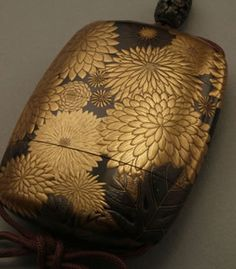 Makie inro, full of chrysanthemums / SHIBATA Zeshin.  An inrō (印籠) is a traditional Japanese case for holding small objects.