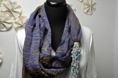 Handwoven textile scarf in shades of blue and gold, with a wonderful cluster of braids and beads. By Amber Kane