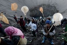 August 4, 2012. People try to catch the various items being thrown into the crater of Mount Bromo. Thousands from different faiths and tourists witnessed the ceremony at Bromo Mountain, East Java, where visitors come to the volcano to make their yearly sacrifices as part of the festival of Yadnya Kasada.