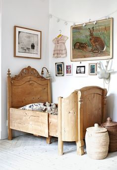 Children's room with antique oak bed, neutral color palette, gallery wall