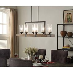 The Vineyard Metal and Wood 6-light Chandelier features a rectangular shaped frame in warm brown wood and distressed bronze metal with seeded glass shades. This is perfect for use in a living room, dining room, or used as island lighting. The chandelier includes a variety of hanging rods to adjust to your home's ceiling height. #homedecor #chandelier