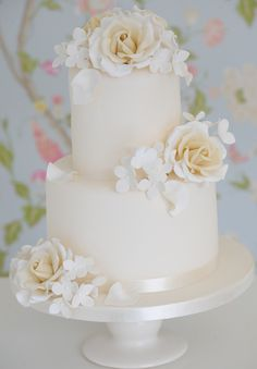 pretty white wedding cake with hand made white edible flowers