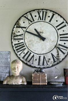 Posés sur la cheminée de la cuisine, un ancien cadran d'horloge, un buste, une pile de livres chinés et une fourmi en papier mâché, création...