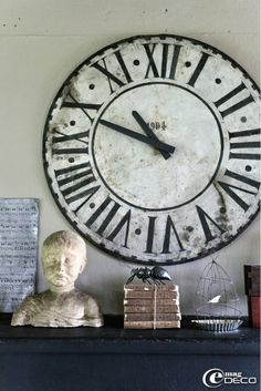 Placed on the fireplace in the kitchen, an old clock face, a bust, a stack of books and an ant antique papier mâché creation Farfelus Farfadets
