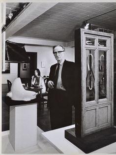 "Marcel Duchamp standing beside Fountain with Eve Babitz in background   Duchamp Retrospective, Pasadena Art Museum, 1963   vintage gelatin silver print 14 x 10.5"" © Julian Wasser"