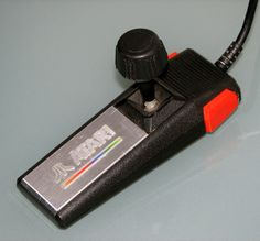 Atari 7800 Joystick :-: Originally released in 1984 with the Atari 7800 Video Game Console, some consider this controller to be ugly and not ergonomic when compared with joysticks of the era. In many ways the device seems to be experimental,  with a very odd aspect ratio in its base. The position of the fire buttons seem badly placed considering the length of the device and how it might likely be held. The top of the stick also seems bulky , but produced excellent control.