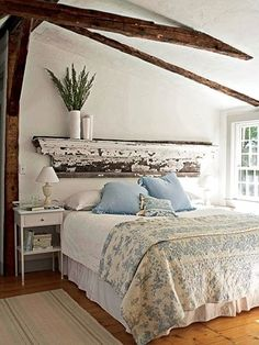 Whatever that old piece of wood shelving is above that bed...i love it. and those ceiling beams!