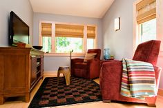 Mid Century - Ski Lodge - Bungalow - Mountain Home - Entertainment Media Console - Carved Wood Stool - Checkered Rug - Marsala Upholstered Chairs - Striped Throw - Blue Vase - Woven Shades Window Treatment - Natural Wood Trim Wall Sconce Geometric - Brown - Black - Marsala