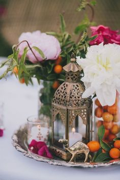 Moroccan inspired centerpiece | silver tray, lantern, candles, flowers and fruit