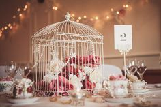 Birdcage with silk flowers, tea cups and butterfly table number holder. Fairy lights and bunting swagged behind. Photo courtesy of Lola Rose Photography