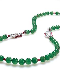Composed of fifty-five jadeite beads of bright green colour, decorated by ruby beads, the clasp set with brilliant-cut diamond, the claps set with brilliant-cut diamonds and rubies, mounted in 18k white gold, largest jadeite bead approximately 10.47 mm, length approximately 68 cm. Accompained by Hong Kong Jade & Stone Laboratory report no. KJ84471 dated 24 February, 2014 stating that the jadeite is natural, known in the trade as 'A Jade'.
