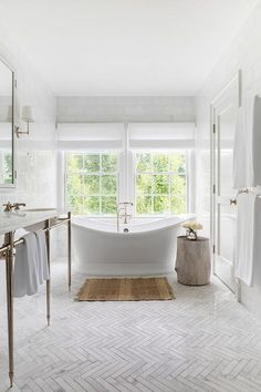 A vintage freestanding bathtub sits on thin marble herringbone pattern floor tiles beneath windows covered in white roman shades in this chic white bathroom. Marble Bathroom Floor, White Bathroom, Bathroom Flooring, Bathroom Interior, Master Bathroom, Freestanding Bathtub, Vintage Bathroom Tiles, Vintage Tile Floor, Family Bathroom