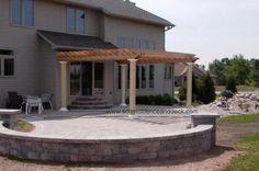 Cedar pergola with fiberglass columns on paver patio.