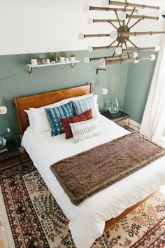 a cozy feeling guest room with sage green and white walls, white linens and a boho rug