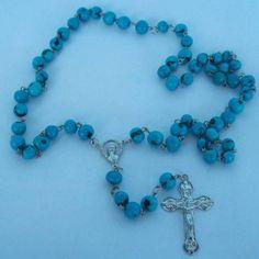 Terço feito com sementes de açaí na cor azul e pingente de metal prateado. R$ 8,00