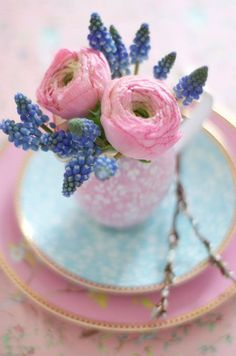 A delicate teapot is filled with purple muscari and two lush ranunculus blooms. #centerpiece #weddingdecor