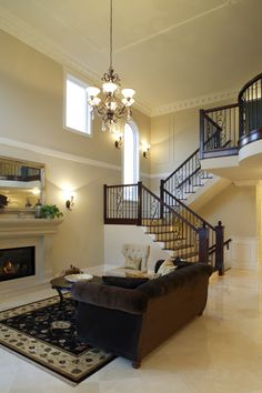 Contrast+between+rich,+dark+wood+tones+and+beige+dominates+this+room.+Light+marble+flooring+is+paired+with+dark+brown+sofa+and+wood+railings+on+staircase+at+right,+while+beige+fireplace+stands+below+singular+chandelier.
