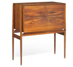 Preben Fabricius was an apprentice of cabinetmaker Niels Vodder, and this was a test piece awarded bronze. Made 1952. Brazilian rosewood cabinet with tall, round, side mounted legs. Front with flip-down leaf, interior with storage space and nine small mahogany drawers, handles and edges of Brazilian rosewood. Fittings and key of brass.
