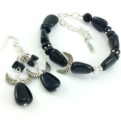 Komplet biżuteriidamskiej wykonany ręcznie. Kolczyki i bransoletkaz czarnych koralików szklanych jablonex i elementów w kolorze srebrnym- w tym mosiężnychskrzydeł.