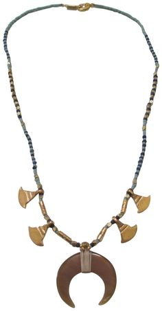 "Chan Luu Blue Beaded and Gold Tone Horn Charm Pendant Necklace. Chan Luu design features a semi precious tiny lapis beaded blue chain adorned with gold tone nuggets and horn charms, larger c curved middle charm is made of a resin material. fastens with a lobster claw closure. necklace measures 17"" in length , gold tone side horns measures approx: 3/8"" , center opaque resin charm measures approx: 1"" across. image may be enlarged to show detail - please refer to product dimensions for…"