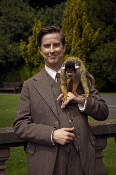 """Lee Ingleby as George Mottershead with Mortimer (1894-1978) the squirrel monkey in BBC One drama """"Our Zoo"""", 2014."""