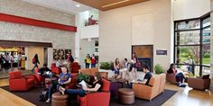 """The campus living room in the Campbell Student Union at Carthage College (Wisc.) serves as a cozy, flexible area for students to gather to study or simply pass time between classes. The high ceilings as well as natural lighting aid in making the room welcoming and bright. The room is part of an open layout that attaches to a """"Main Street"""" corridor with retail venues, and the building includes a theater, bookstore, and gaming areas, as well. The soft color palette and fireplace add to the ..."""