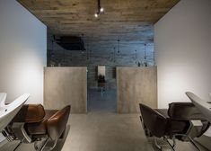 Oak boards cover the chamfered entrance to this hair and beauty salon in Osaka, renovated by Okuwada Architects Office to look like a cave