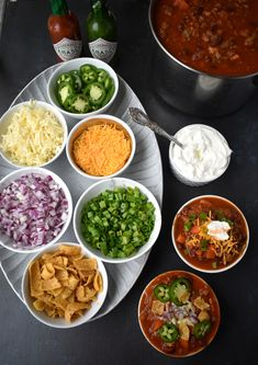Ultimate Chili Bar features a spicy turkey chili and all the toppings including shredded cheese red onions jalapenos hot sauce corn chips sour cream and green onions Perf. Chili Bar Party, Nacho Bar, Slow Cooker Chili, Strudel, Sour Cream, Fall Recipes, Dinner Recipes, Delicious Recipes, Barbecue