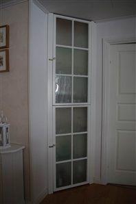 Inbyggt skåp med vitrindörrar