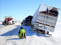 A tow truck pulls a semi-truck onto the road  in Greensburg, Kansas.