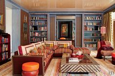 In the library of a colorful Russian dacha designed by Gabhan O'Keeffe, part of the book collection is displayed on built-in wenge-wood shelves stained denim-blue.