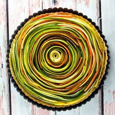 Thinly sliced summer vegetables are the visual star of this spiral vegetable tart with a layer of homemade sundried tomato pesto and a flaky pie crust.