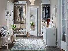 Ein Flur u. a. mit einem ELVARLI Element in Weiß mit Böden und Kleiderstangen für Jacken, Taschen und Schuhe, dazu eine weiße Kommode und eine weiße Bank