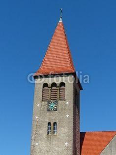 Kirchturm mit Turmuhr vor blauem Himmel in Helpup bei Detmold im Kreis Lippe