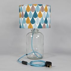 A deliciously colourful table lamp, hand-crafted from an upcycled demijohn bottle.Mid century illustrator Charley Harper was the inspiration behind this shade's vibrant leaf print in blues, grey and gold. This deliciously colourful table lamp is hand-crafted from an upcycled demijohn bottle. It is wired with a fabric covered cable and a chrome lamp holder. As with all Humblesticks products, it's ethically produced, handmade and upcycled.The base is an upcycled clear glass demijohn bottle…