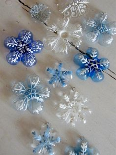 Cut the bottoms off of water/soda bottles, paint on a snowflake design with a q-tip or small paintbrush, punch a small hole in the top and add a hook. Cute Christmas Snowflake ornaments!