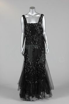 An elaborate black beaded and sequined tabard, circa 1918, mounted onto a black satin petticoat with tulle hem in the 1930s, with sequined design of trailing flowerheads, the bodice and hem with deep bands of square sequins