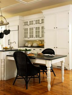 Island Extension: Place a short side table next to the island in matching colors -- in this kitchen, that means a white base and a black countertop. An island extension such as this offers a place for eating meals and doing homework -- and food prep that's easier to do sitting down, such as frosting cookies or cupcakes