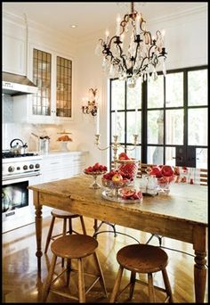 Kitchen - high ceilings, white walls, black framed doors, white cabinets and tops, leaded glass doors, wall wood table and stools, black iron chandelier